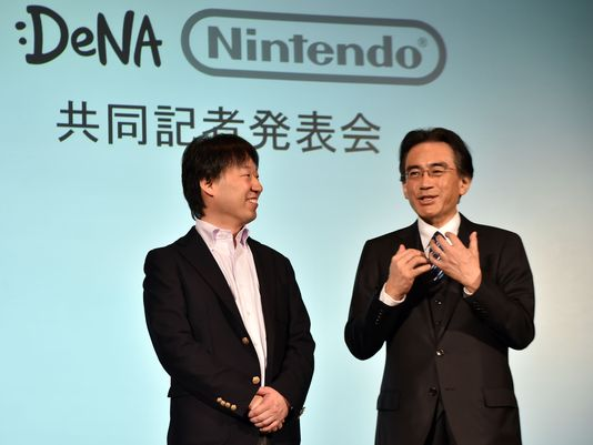 Japan's video game giant Nintendo president Satoru Iwata speaks as Japanese online game operator DeNA president Isao Moriyasu, left, looks on at a press conference in Tokyo on March 17, 2015. (Foto: Yoshikazu Tsuno / Getty Images)