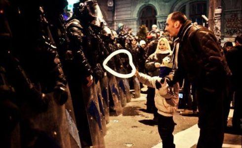 Un bimbo porge un palloncino a forma di cuore alla polizia anti-sommossa