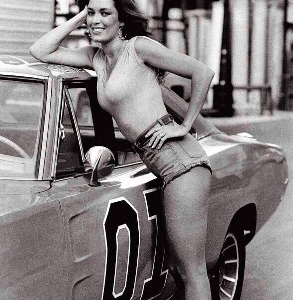 "Catherine Bach di fianco al al mitico ""Generale Lee"", una Dodge Charger del 1969, in The Dukes of Hazzard"