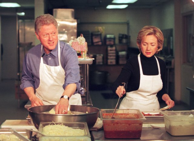 President Bill Clinton and wife Hillary work at the DC Central Kitchen making lasagna to feed the homeless December 21, 1998. Photograph by Richard Ellis—Getty Images